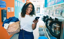 Young african american woman with curly hair smiling happy doing chores at the laundry using phone