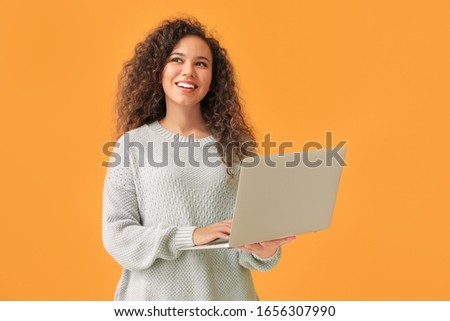 Young African-American woman with laptop on color background