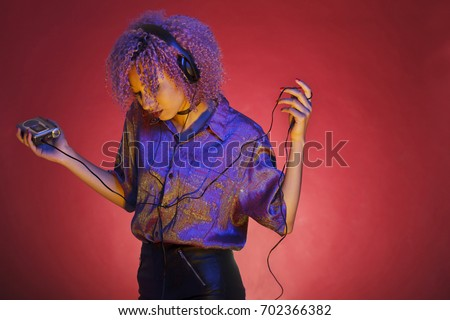 Photo of  young african american woman with vintage clothes listening to music with her walkman