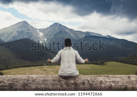 Young African Americans guy sitting on a big log with hands apart and looking at the beautiful panorama of the mountains before the storm, concept of inspiration, enthusiasm and aspiration #1194472666