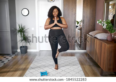 young african black woman keep balance, stand on one leg, yoga time at home. concentrated on yoga, meditation