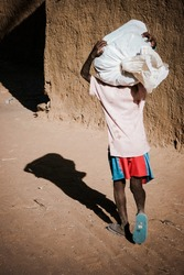 Young african boy carrying a bag, back view