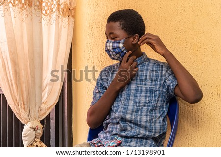 young african boy child wearing a homemade face mask he made himself