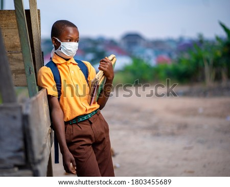 young African boy in uniform, with back pack and books in the hand-Black guy with face mask-out door school concept