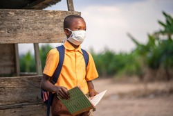 young African boy in uniform, with back pack and  opened book-Black guy with face mask-out door school concept