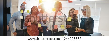Young African businessman brainstorming with sticky notes on a glass wall with his team while working together in a modern office