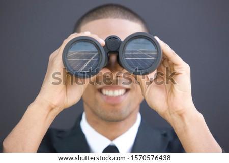 Young African businessman looking through binoculars