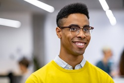 Young african businessman smiling while standing in co-working office. Close up face of successful black man looking away and laughing. Portrait of university nerd student with big grin.