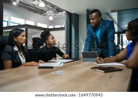 Young African businessman talking with a diverse group of female colleagues during a meeting around a table in an office boardroom