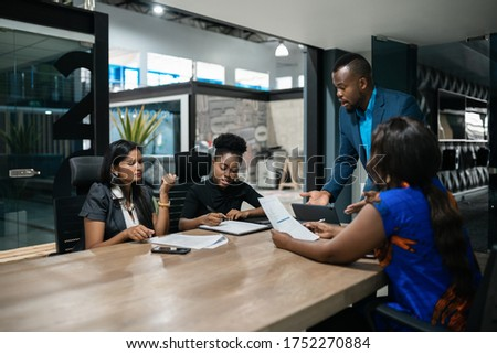 Young African businessman talking with a diverse team of colleagues during a meeting around a table in an office boardroom