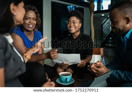 Young African businesspeople laughing together while going over paperwork during a casual meeting in an office