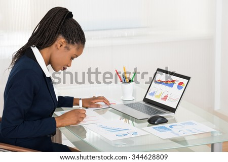 Young African Businesswoman Analyzing Graph While Laptop On Office Desk