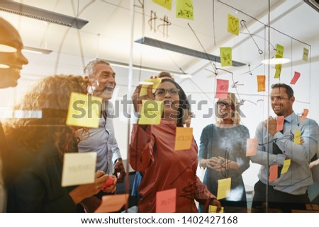 Young African businesswoman and her diverse team brainstorming with sticky notes on a glass wall while working together in a modern office #1402427168