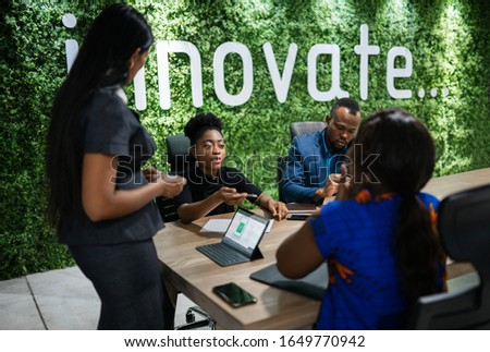 Young African businesswoman talking with a group of work colleagues during a meeting together around a table in an office boardroom