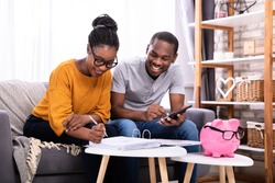 Young African Couple Sitting On Sofa Calculating Invoice