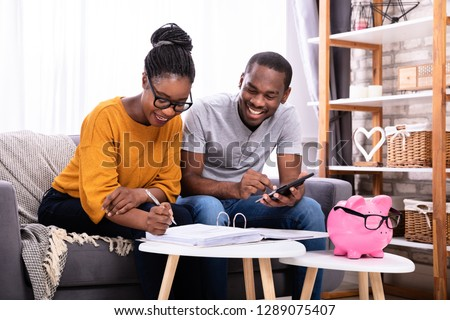 Young African Couple Sitting On Sofa Calculating Invoice Stockfoto ©