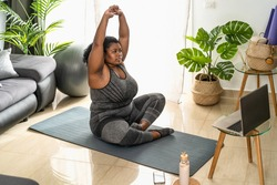 Young African curvy woman doing pilates online fitness class with laptop at home - Sport wellness people lifestyle concept