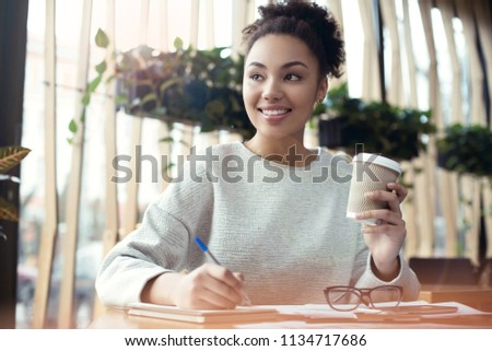 Young african descent woman working at creative stylish office sitting at the table drinking hot latte coffee looking aside dreaming writing plan for day smiling inspired close-up bottom view
