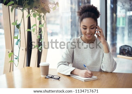 Young african descent woman working at creative stylish office sitting at the table talking on phone writing tasks to do in notebook planner smiling cheerful