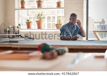 Young African design entrepreneur talking on phone in workshop