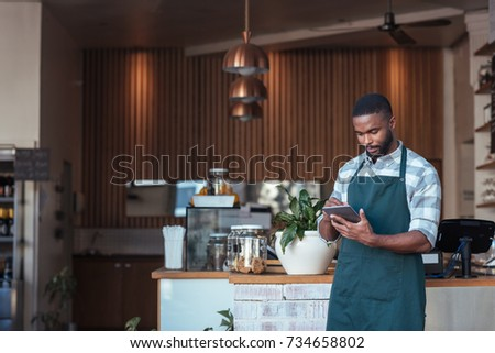 Young African entrepreneur in an apron using a digital tablet while standing in front of the counter of his trendy cafe