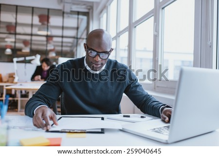 Young african executive sitting at his desk with laptop reading a document. African man working in office.