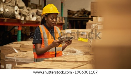 Young African female warehouse worker working on a digital table during an iventory check Stock foto ©