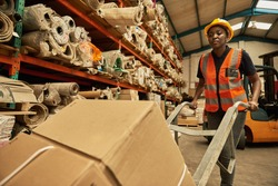Young African female worker walking with a dolly of boxes around the floor of a textile warehouse