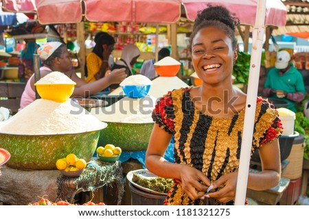 young african girl smiling in a local african market