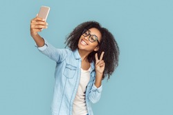 Young african girl wearing eyeglasses standing isolated on gray background taking selfie photo on smartphone posing to camer showing peace gesture smiling happy