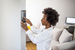 Young african girl woman lady adjusting remote climate control panel settings wall touch screen set heating conditioning switch on security system energy saving mode, black lady use smart home concept