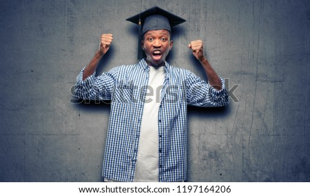 Young african graduate student black man happy and excited celebrating victory expressing big success, power, energy and positive emotions. Celebrates new job joyful