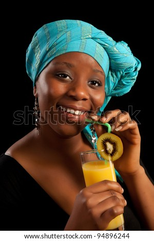 Young African lady drinking orange juice and wearing traditional ghanese scarf