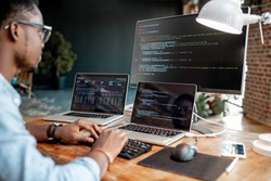 Young african male programmer writing program code sitting at the workplace with three monitors in the office. Image focused on the screen
