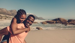 Young african man carrying his girlfriend on his back at the beach. Loving couple having piggyback fun on seaside.