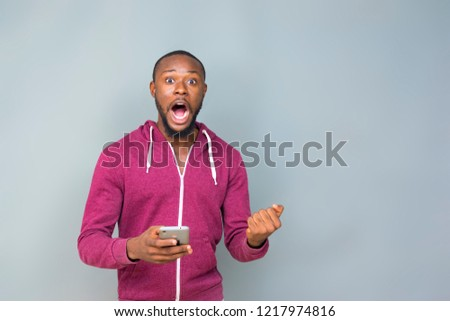 young african man excited and celebrating while holding his phone  #1217974816