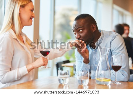 Young African man gives his girlfriend a hand kiss in the restaurant #1446971093