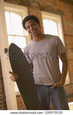 Young African man holding skateboard