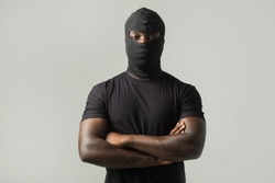 young african man in a black mask and a black t-shirt on a gray background