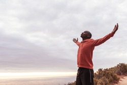 Young African man in a hoodie standing with his arms raised to the sky while out for a cross country run by the ocean