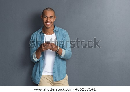 Young african man leaning against a grey wall using mobile phone. Portrait of a happy laughing guy texting a phone message and looking at camera. Man reading a message on cell phone with copyspace. #485257141