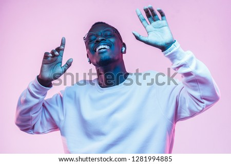 Young african man listening to music with wireless earphones and dancing isolated on pink background #1281994885