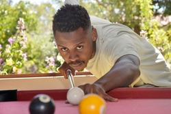Young African man playing a game of billiards or pool during lockdown 2020, #stayhome, #socialdistancing, #lockdown, #home entertainment
