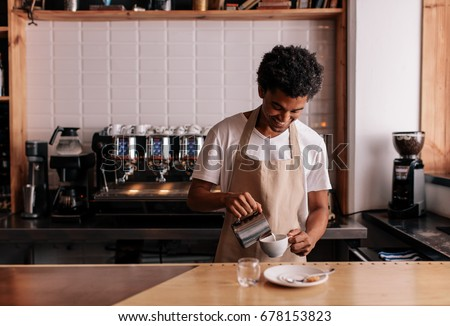 Young african man pouring milk into coffee making espresso. Professional barista preparing coffee on counter.