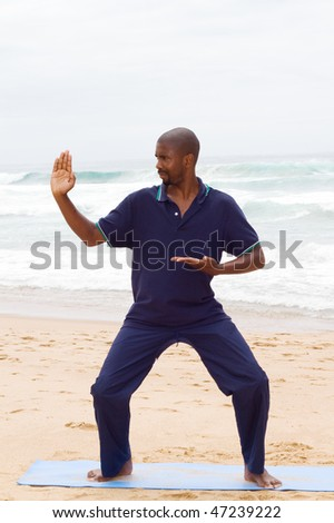 young african man practicing tai chi on beach