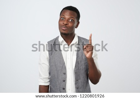 Young african man raises index finger as gets idea how to make interesting project. Creative man has something on his mind