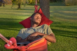 Young African man relaxing and sleeping in hammock with book on his chest. Outdoor garden scene and summer season. Park like setting
