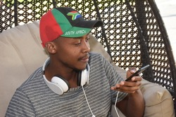 Young African man watching sport on smart phone with head phones wearing South African flag cap as loyal supporter. #southafrican  #covid 19  #stayhome. #selfisolation