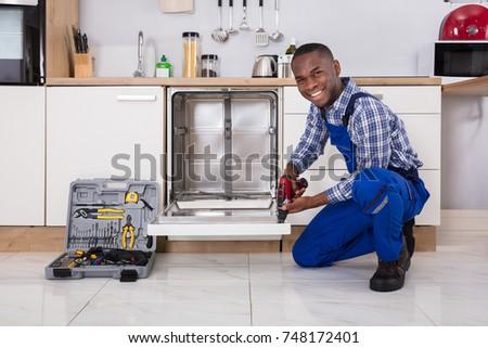 Young African Repairman Fixing Dishwasher In Kitchen