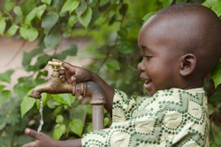 Young African school boy holding hands under a tap. Water scarcity problems concern the inadequate access to safe drinking water. 1 billion people in the developing world don't have access to it.